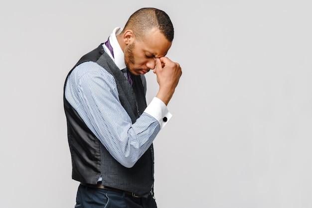 Joven empresario afroamericano tocando la cabeza debido a dolor de cabeza y estrés