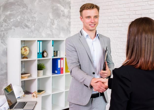 Joven empresario agitando una mano de mujer