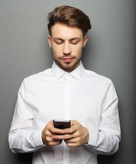 Joven empresario alegre escribiendo sms en su teléfono móvil