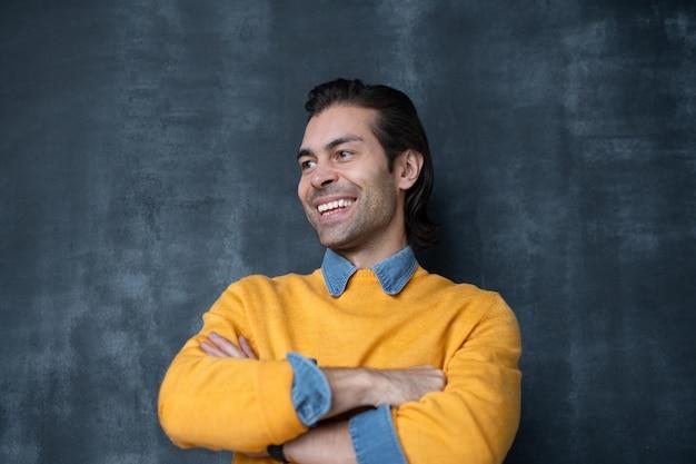 Joven empresario alegre con una gran sonrisa manteniendo los brazos cruzados por el pecho mientras está de pie contra la pizarra de forma aislada