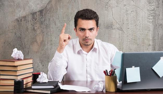 Joven empresario apuntando al revés en el escritorio de oficina.