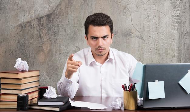 Joven empresario apuntando a la cámara en el escritorio de oficina.