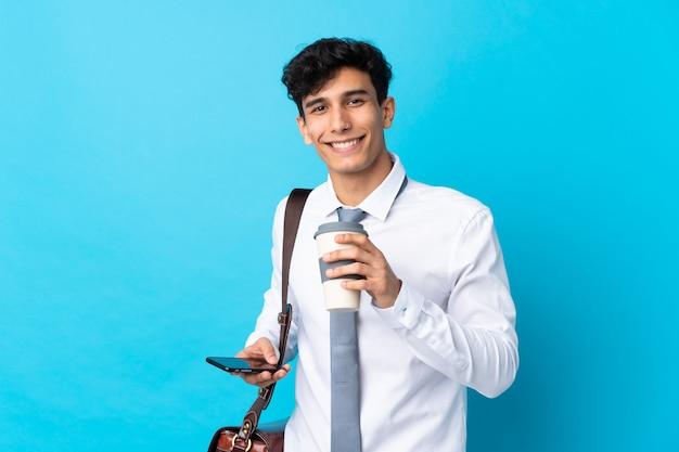 Joven empresario argentino sobre pared azul aislado