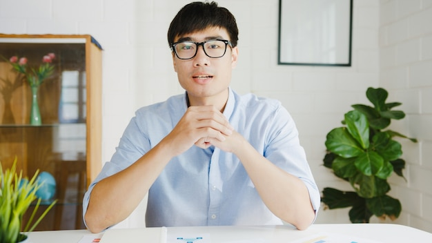Joven empresario de asia con computadora portátil hablar con colegas sobre el plan en la reunión de videollamada mientras trabaja desde casa en la sala de estar autoaislamiento, distanciamiento social, cuarentena por coronavirus.