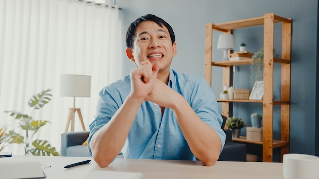 Joven empresario de asia con computadora portátil hablar con colegas sobre el plan en la reunión de videollamada mientras trabaja desde casa