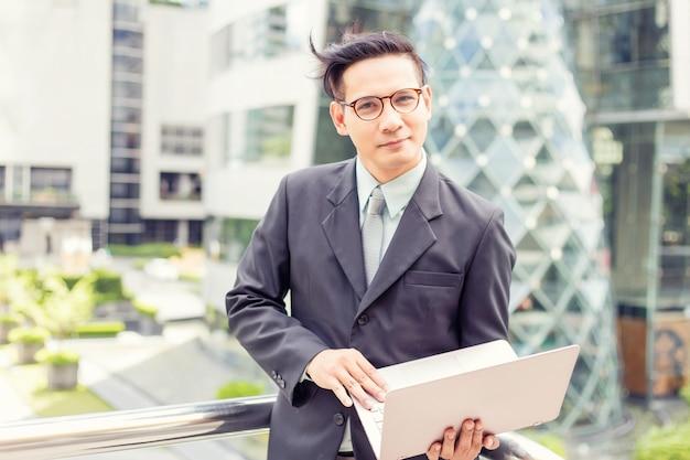 Joven empresario de asia en traje con su computadora portátil al aire libre