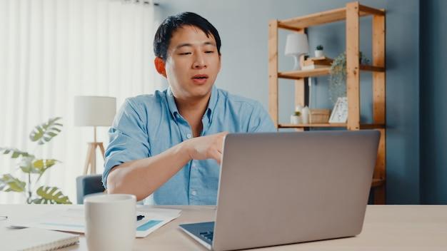 El joven empresario de asia usando una computadora portátil habla con sus colegas sobre el plan en la videollamada mientras trabaja de manera inteligente desde casa en la sala de estar.