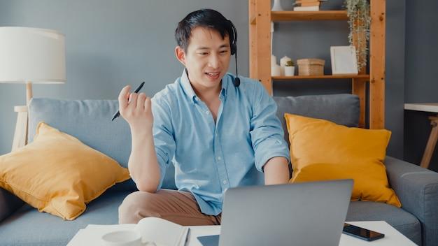 Joven empresario asiático con auriculares usando una computadora portátil y habla con sus colegas sobre el plan en la videollamada