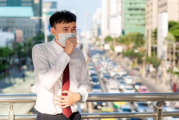 Joven empresario asiático con camisa blanca que va a trabajar sintiéndose enfermo de tos, usa una máscara de protección para evitar el polvo pm2.5, el smog, la contaminación del aire y covid-19 con atascos en bangkok, tailandia