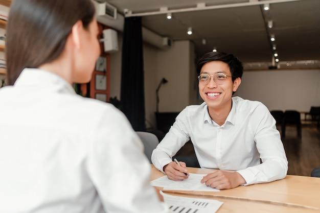 Joven empresario asiático en la entrevista de trabajo con una mujer en la oficina