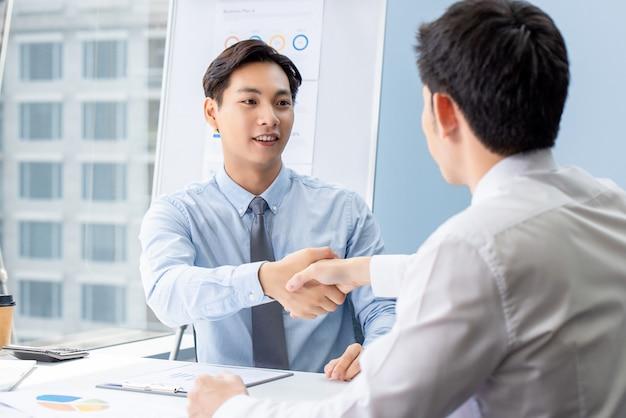 Joven empresario asiático haciendo apretón de manos con pareja