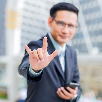 Joven empresario asiático haciendo un gesto de cuerno pesado firmar con las manos