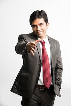 Joven empresario asiático indio ofreciendo o acercándose para apretón de manos, aislado sobre fondo blanco.