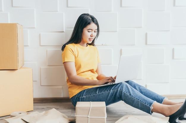 El joven empresario asiático inicia el propietario del vendedor en línea usando una computadora para verificar los pedidos de los clientes por correo electrónico o sitio web y preparar paquetes