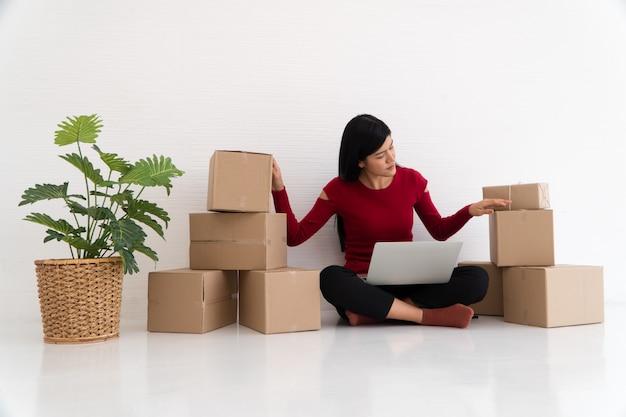 Joven empresario asiático que siente estrés y ansiedad como resultado de la reducción de ventas después de verificar los pedidos de los clientes