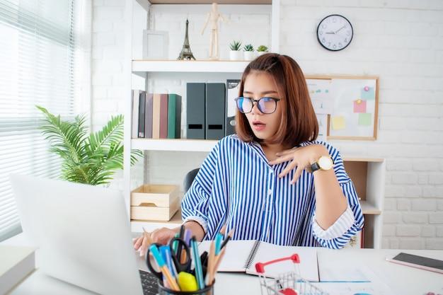 El joven empresario asiático se sorprendió por el mensaje en la computadora portátil en la oficina.