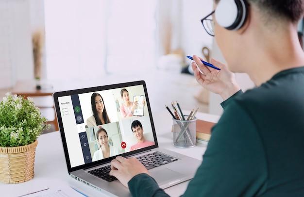 Joven empresario asiático usa auriculares trabajando de forma remota desde casa y reunión de videoconferencia virtual con colegas empresarios. distanciamiento social en el concepto de oficina en casa.