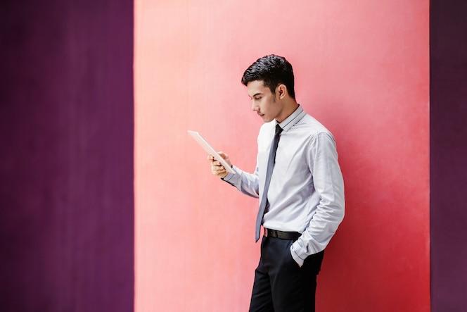 Joven empresario asiático y feliz leyendo o trabajando en tableta