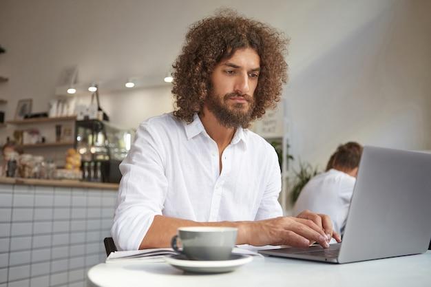 Joven empresario atractivo con cabello castaño rizado posando sobre el interior del café, trabajando fuera de la oficina con un portátil moderno, mirando fijamente al monitor