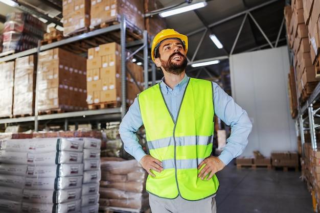 Joven empresario atractivo sonriente en chaleco con casco protector de pie en el almacén con las manos en las caderas y mirando hacia arriba.