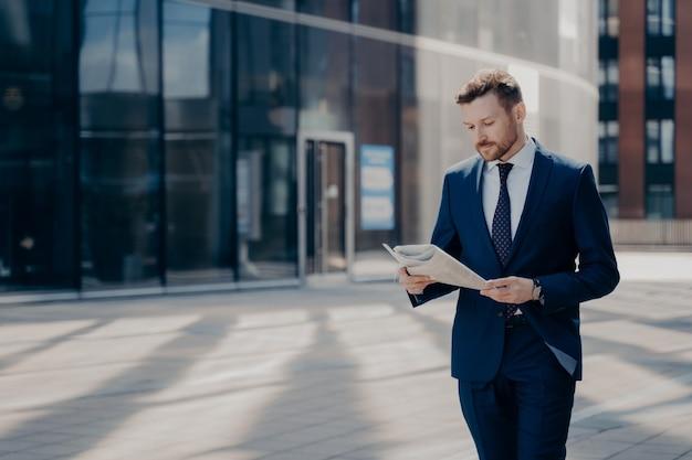 Joven empresario barbudo concentrado en traje formal caminando solo con el periódico en las manos, leyendo las últimas noticias en su camino al lugar de trabajo con edificios de oficinas en segundo plano.
