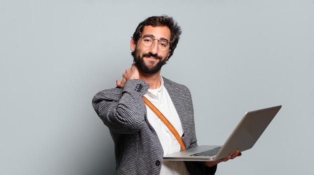 Joven empresario barbudo y loco con un portátil