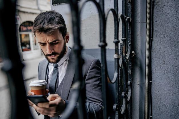 Joven empresario barbudo de pie junto a una vieja valla de hierro en la fuente del edificio, sosteniendo la taza con café recién hecho por la mañana y escribiendo un mensaje en el teléfono inteligente.