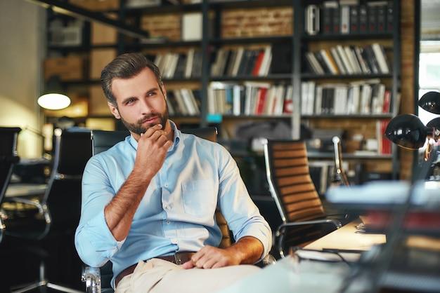 Joven empresario barbudo en ropa formal tocando su barbilla y pensando en algo