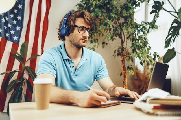 Joven empresario barbudo sentado a la mesa con ordenador portátil y bandera americana
