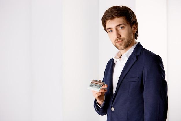Joven empresario barbudo en traje con dinero, sonriendo mientras sugiere un buen salario, ingresos estables, buscando empleados para la compañía