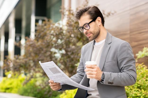 Joven empresario bien vestido con café y periódico pasando la mañana en el entorno urbano