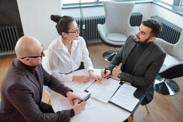 Joven empresario bien vestido con lápiz sobre contrato que va a firmar el documento mientras consulta con un socio comercial