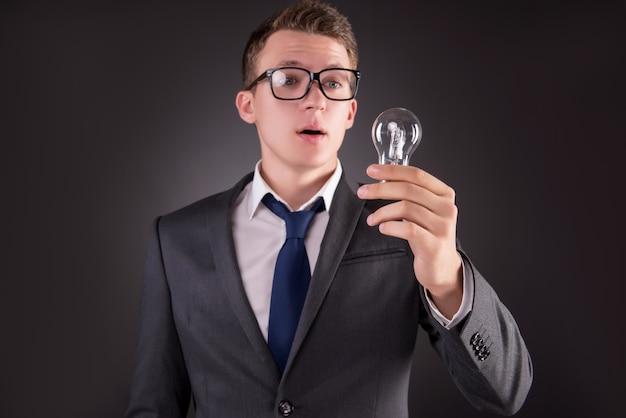 Joven empresario con bombilla en concepto de idea