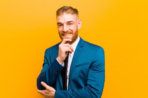 Joven empresario de cabeza roja mirando feliz y sonriente con la mano en la barbilla, preguntándose o haciendo una pregunta, comparando opciones