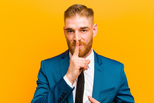 Joven empresario de cabeza roja mirando serio y cruzado con el dedo presionado a los labios exigiendo silencio o silencio manteniendo un secreto sobre fondo naranja