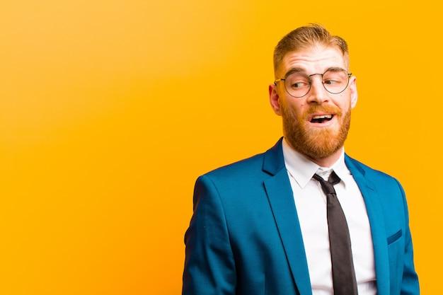 Joven empresario de cabeza roja se siente sorprendido, feliz, asombrado y sorprendido, mirando hacia el lado con la boca abierta