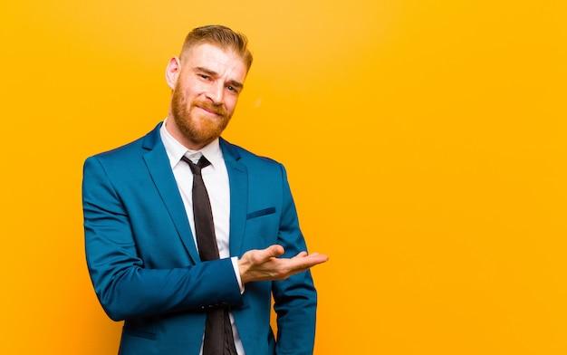 Joven empresario de cabeza roja sonriendo alegremente, sintiéndose feliz y mostrando un concepto en el espacio de la copia con la palma de la mano sobre fondo naranja