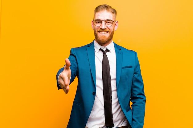 Joven empresario de cabeza roja sonriendo, luciendo feliz, confiado y amable, ofreciendo un apretón de manos para cerrar un trato, cooperando en naranja