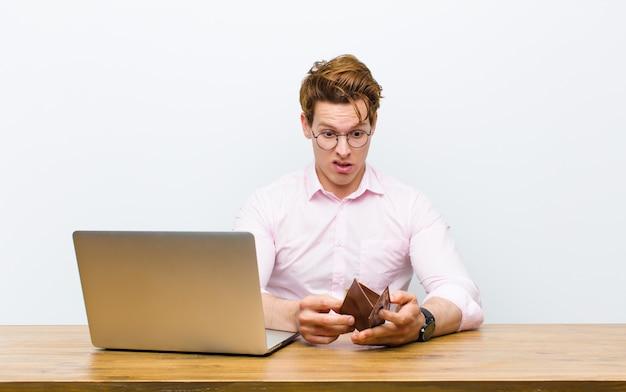 Joven empresario cabeza roja trabajando en su escritorio, concepto de dinero