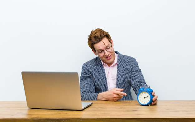 Joven empresario cabeza roja trabajando en su escritorio con un reloj. hora
