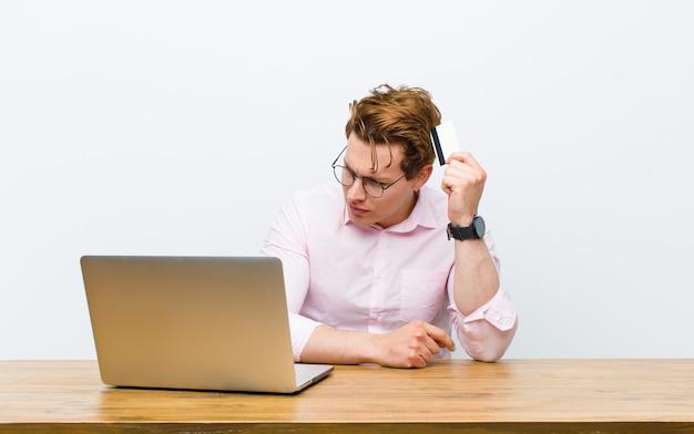 Joven empresario cabeza roja trabajando en su escritorio con una tarjeta de crédito