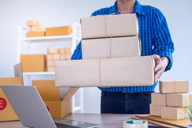Un joven empresario con una caja para enviar productos a los clientes. los vendedores en línea aceptan pedidos a través del sitio web. pequeña empresa familiar, concepto de comercio electrónico