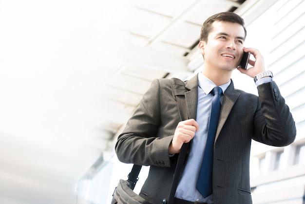 Joven empresario caminando y hablando por teléfono móvil