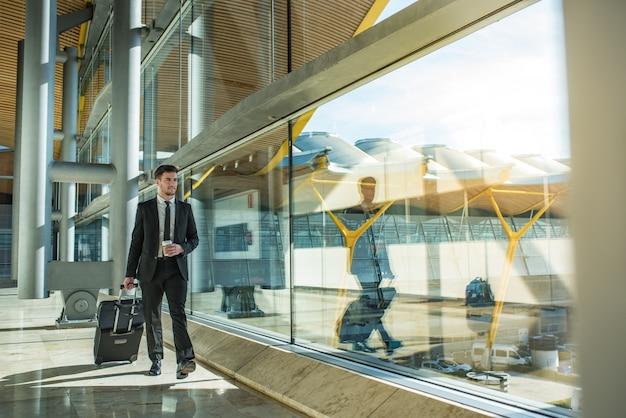 Joven empresario caminando en la terminal del aeropuerto con equipaje sonriendo con un café