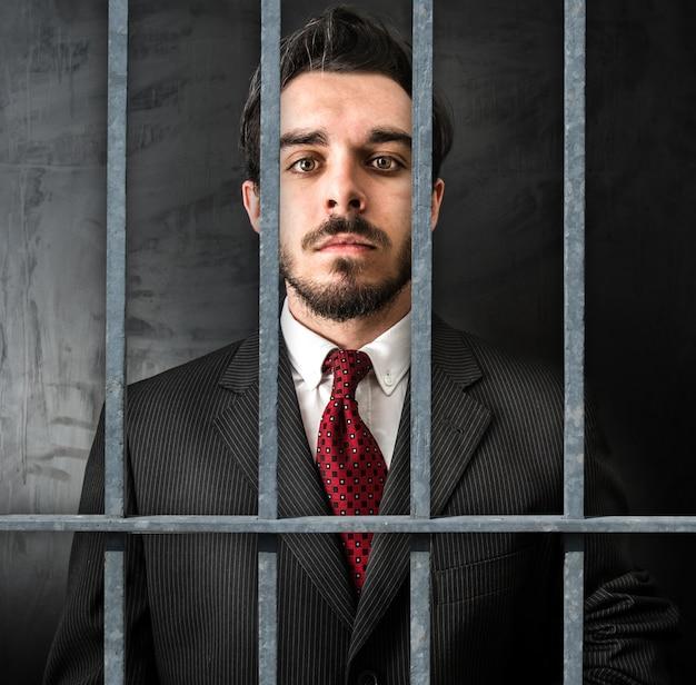 Joven empresario en la cárcel en la oscuridad