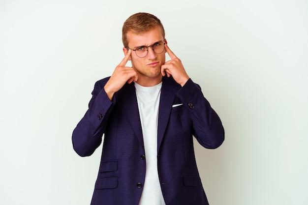 Joven empresario caucásico aislado sobre fondo blanco se centró en una tarea, manteniendo los dedos índice apuntando la cabeza.
