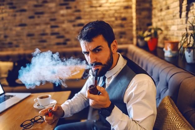 Joven empresario caucásico atractivo serio en traje sentado en la cafetería y pipa en descanso