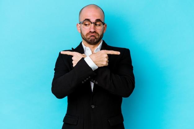Joven empresario caucásico calvo aislado sobre fondo azul apunta hacia los lados, está tratando de elegir entre dos opciones.