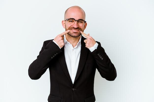 Joven empresario caucásico calvo aislado sobre fondo azul sonríe, señalando con el dedo a la boca.