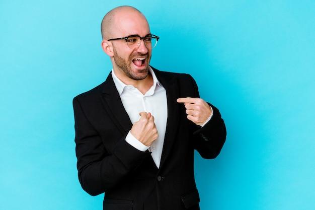 Joven empresario caucásico calvo aislado sobre fondo azul sorprendido señalando con el dedo, sonriendo ampliamente.